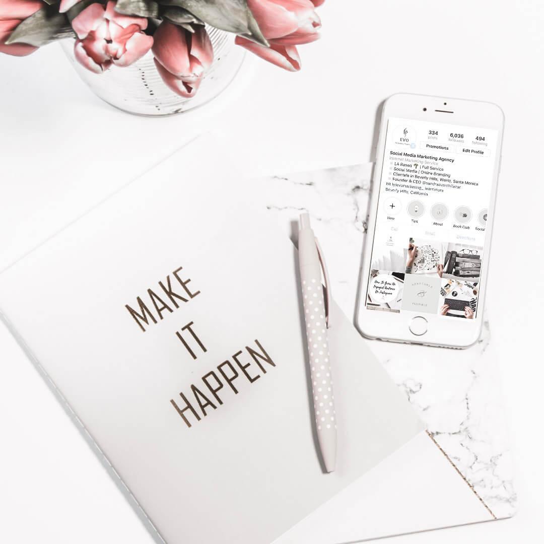 make it happen notebook & iPhone showing Instagram